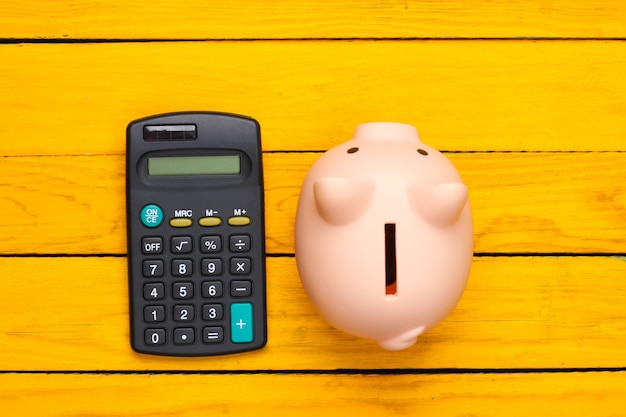 Piggy bank and calculator on a yellow wooden surface. top view
