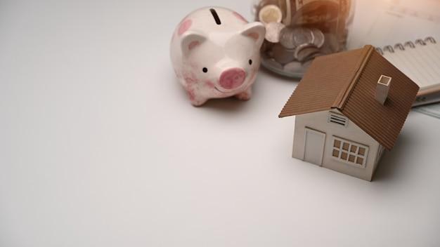 白いテーブルに貯金箱、コイン、家のモデル。将来のためにお金を節約し、家や不動産市場を買うための節約。