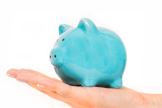 Piggy bank in female hand isolated on white