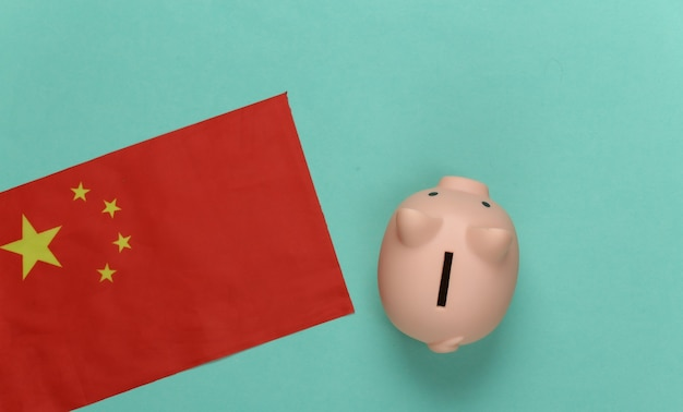 Piggy bank and flag of china on a mint green