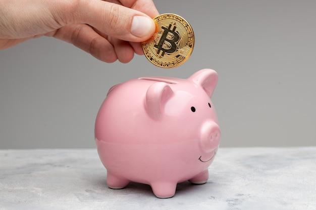 Копилка для биткойнов. мужчина держит в руках валюту и кладет биткойн в копилку на сером фоне.