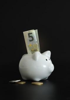 お金を節約するための貯金箱。富、予算、投資、財務の概念。貯金箱、黒の背景に貯金箱。 Premium写真