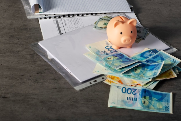 イスラエルの新シェケルとドルの紙幣でお金を節約するための貯金箱がテーブルにあります。灰色の机の上にアメリカとイスラエルのお金で机の上にお金とビジネス文書を節約するための貯金箱