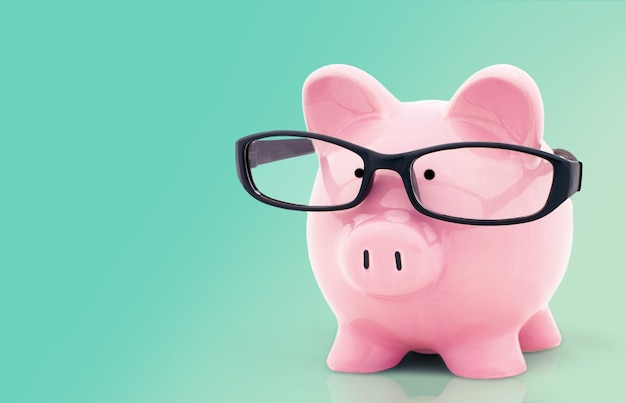 Piggy bank in glasses on background