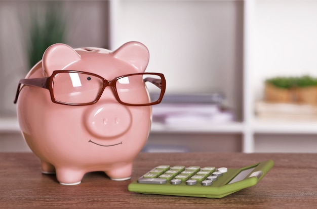 Piggy bank in glasses with calculator on home or office