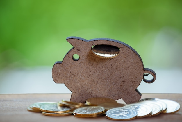 Piggy bank and golden coins on wood table