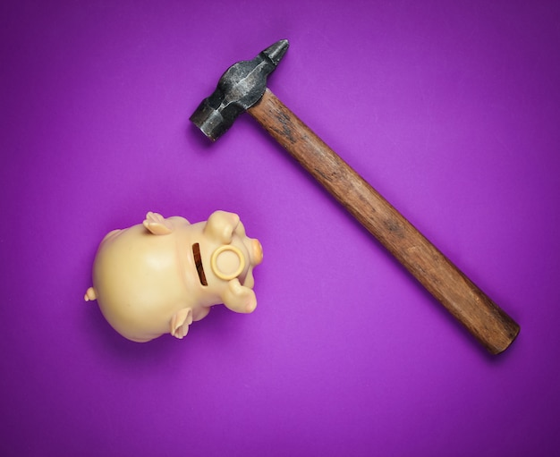 Piggy bank and hammer on purple.