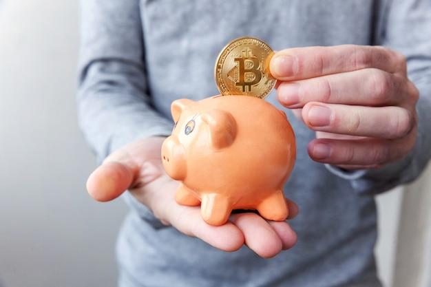 Piggy bank, hand holds golden bitcoin coin virtual money