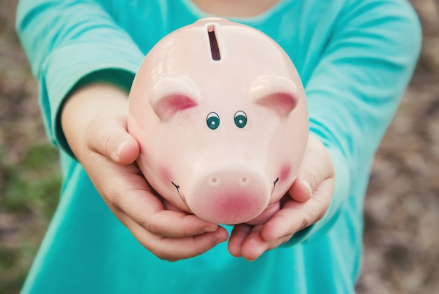 Piggy bank in the hands of a child.