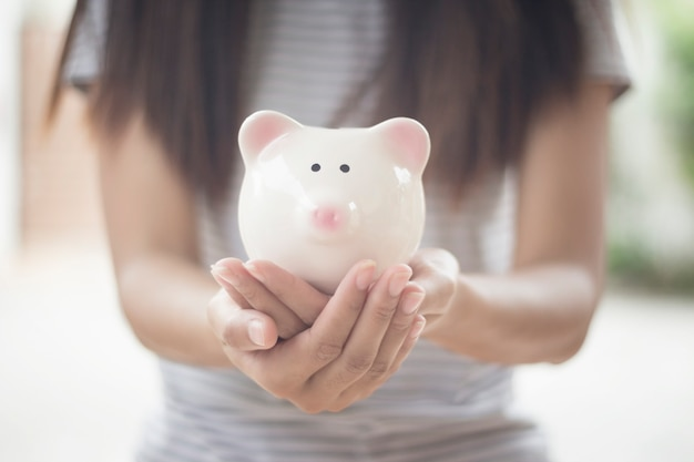 Piggy bank in hands on empty space background