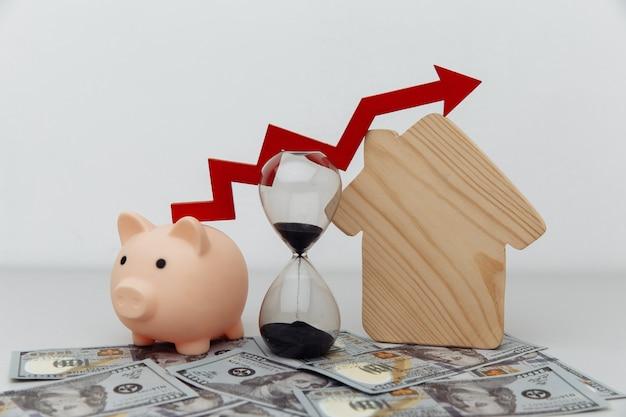 달러 지폐 저장 또는 구매 집 또는 부동산 소유자 개념에 대 한 대출에 위쪽 화살표와 목조 주택 모델 돼지 저금통 모래 시계