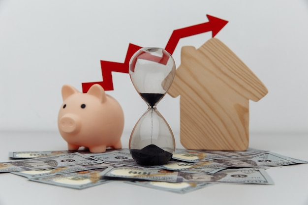 Piggy bank hourglass with arrow up and wooden house models on dollar cash