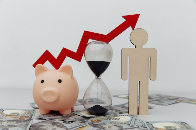 Piggy bank hourglass and wooden person with arrow up on dollar banknotes investment and savings concept