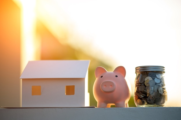 Piggy bank and a house model,concept saving money for house and real estate.
