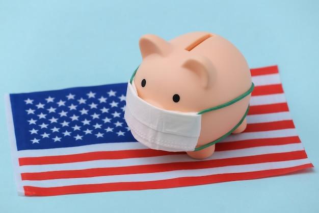 파란색 배경에 미국 국기가 달린 의료용 마스크를 쓴 돼지 저금통. 팬데믹 코로나19