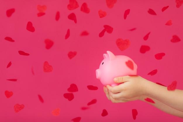 Копилка в руках детей с красным конфетти в форме сердца на розовом фоне концепция день святого валентина