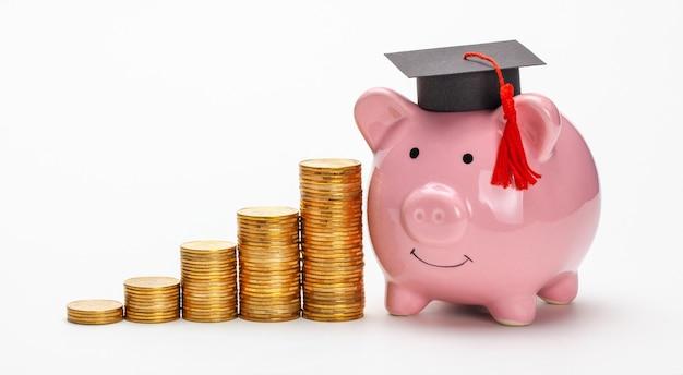 Копилка в кепке выпускника возле стопки монет экономия на образование цены на высшее образование