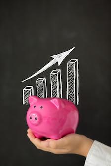 成長するチャートで黒板に対して手に貯金箱
