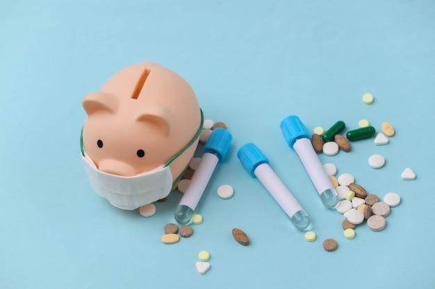 의료용 마스크를 쓴 돼지 저금통, 파란색 배경에 알약이 있는 시험관
