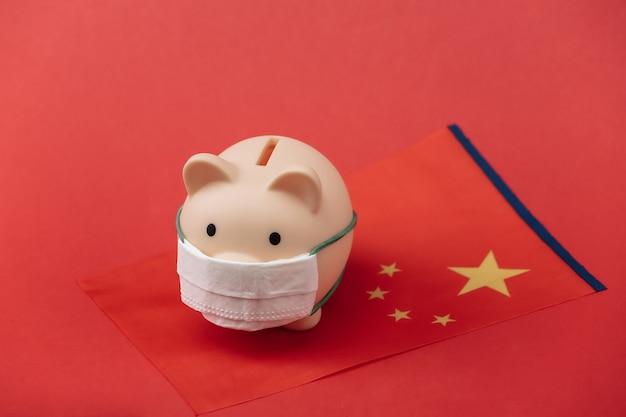 빨간색 배경에 중국 국기가 달린 의료용 마스크를 쓴 돼지 저금통. 팬데믹 코로나19
