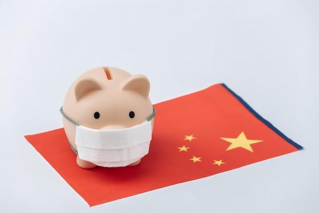 흰색 바탕에 중국 국기가 달린 의료용 마스크를 쓴 돼지 저금통. 팬데믹 코로나19