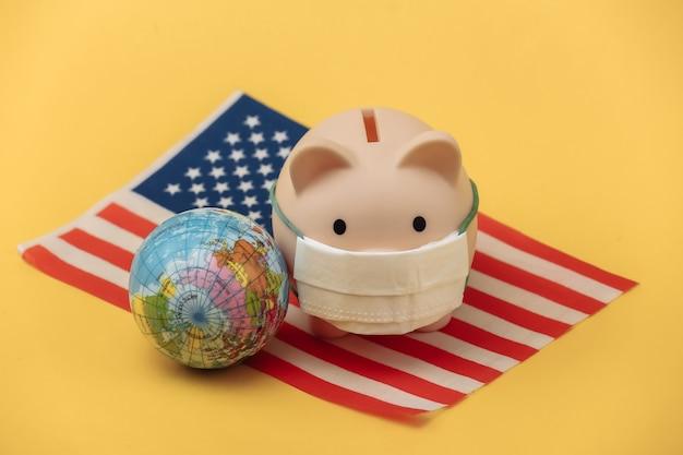 노란색 배경에 미국 국기와 글로브가 있는 의료용 마스크를 쓴 돼지 저금통. 팬데믹 코로나19