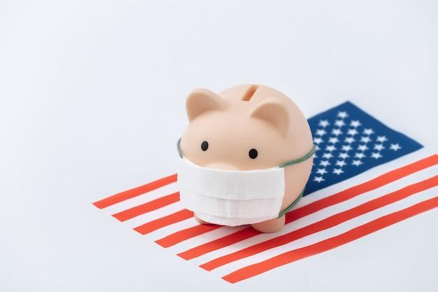 흰색 바탕에 미국 국기가 달린 의료용 마스크를 쓴 돼지 저금통. 팬데믹 코로나19