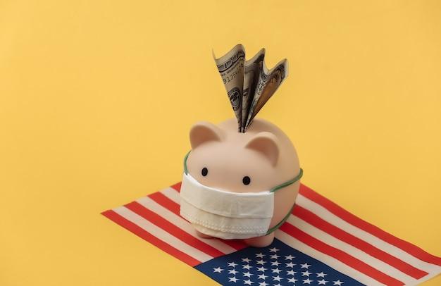노란색 배경에 미국 국기가 달린 의료용 마스크를 쓴 돼지 저금통. 팬데믹 코로나19