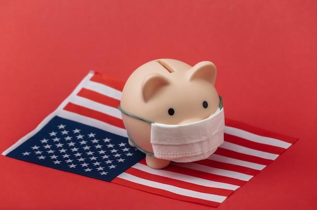 빨간색 배경에 미국 국기가 달린 의료용 마스크를 쓴 돼지 저금통. 팬데믹 코로나19