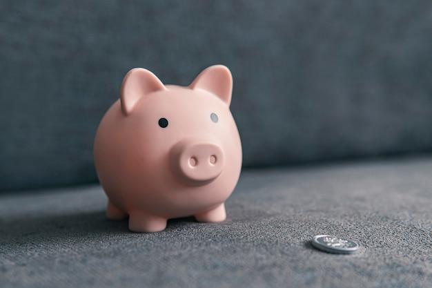 Копилка в виде свиньи и серебряной монеты на темном фоне с копией пространства