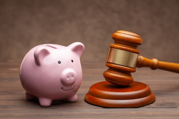 Piggy bank and judge gavel on wooden brown background.