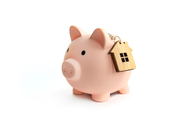 Piggy bank and key house isolated against white background. the concept of saving up for your real estate. save on rent.