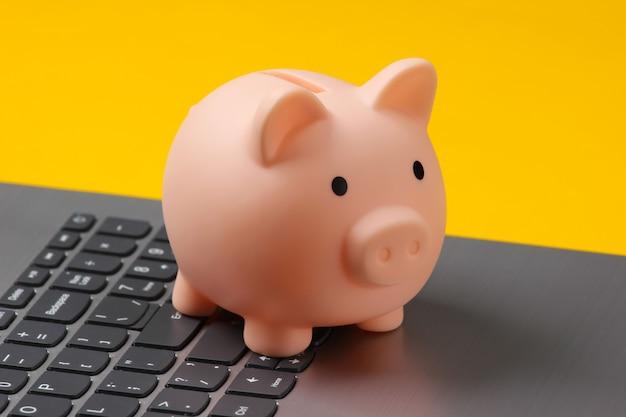 Piggy bank on laptop keyboard closeup