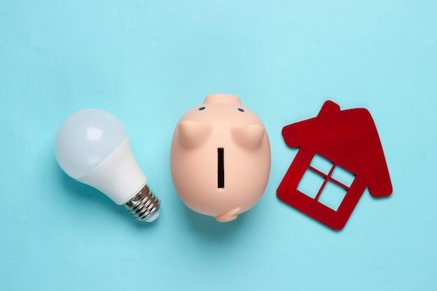 Piggy bank and led light bulb, house figure on blue Premium Photo