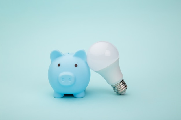 Piggy bank and light bulb on blue background. energy savings concept