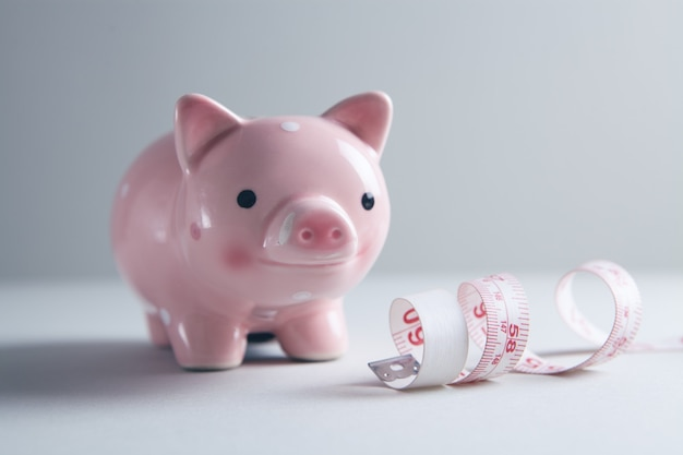 Piggy bank and measuring tape on the table