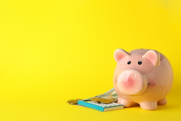 Piggy bank, money and calculator on yellow, space for text