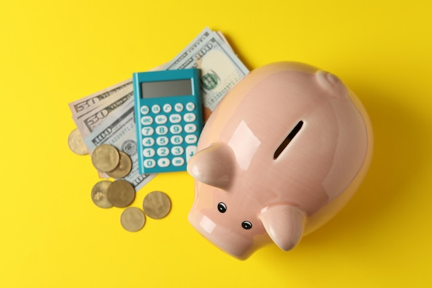 Piggy bank, money and calculator on yellow surface