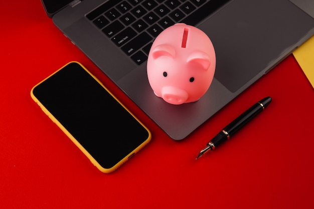 Piggy bank near laptop and smartphone