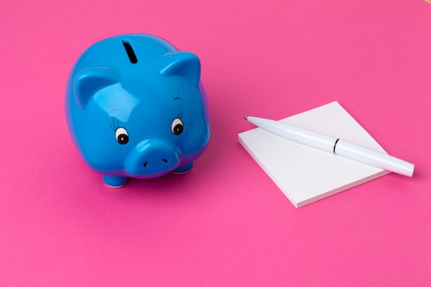 Piggy bank and notebook with a pen