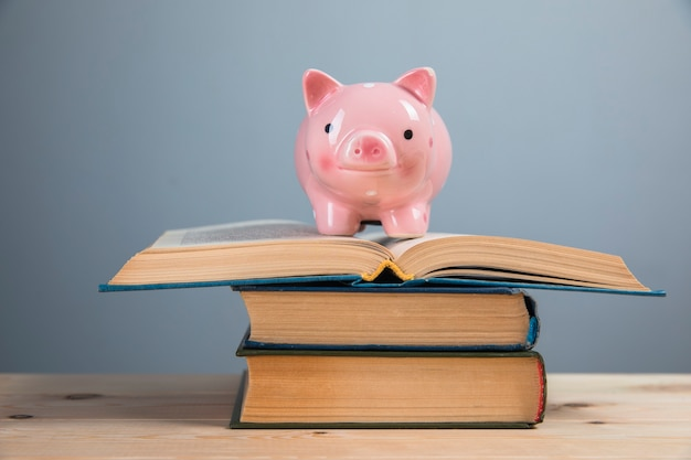 돼지 저금통과 회색 벽에 책
