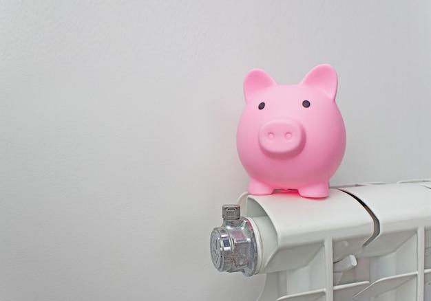 Копилка на радиаторе. сохранение энергии. экономное отопление зимой. дорогая концепция затрат на отопление.