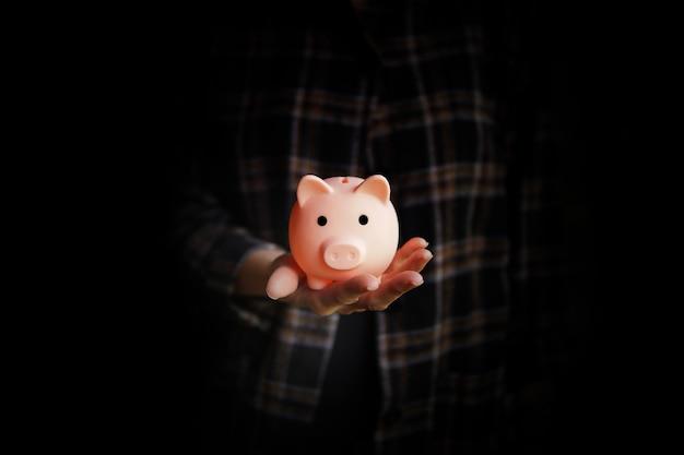 女性の手に貯金箱。お金の節約の概念。