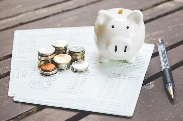 Piggy bank, papers, pen and stack of coins