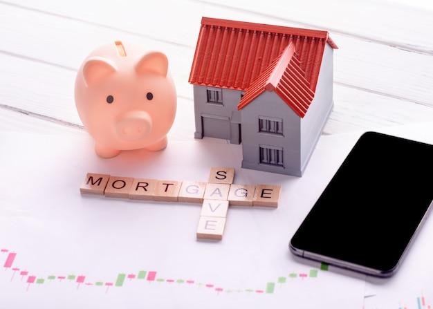貯金箱、電話、住宅ローンのチャートとタイトルの住宅ローンの家と保存