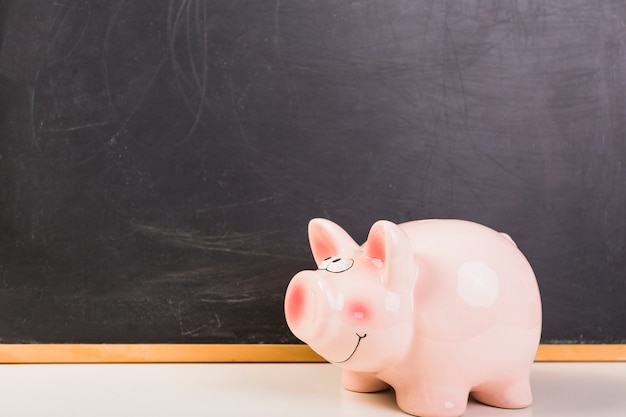 Piggy bank placed at chalkboard