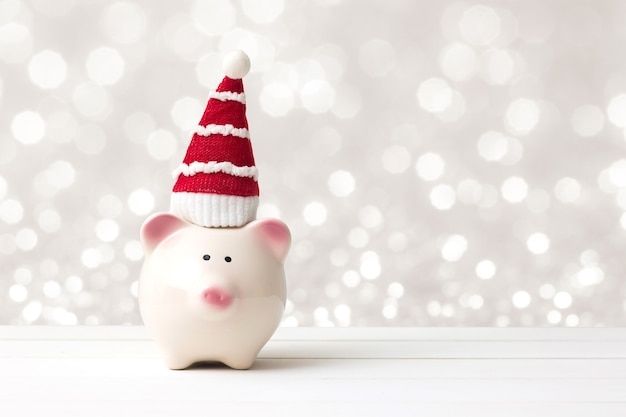 Piggy bank and santa claus hat over white wooden table abstract bokeh light background with copy space. saving and christmas holiday concept.