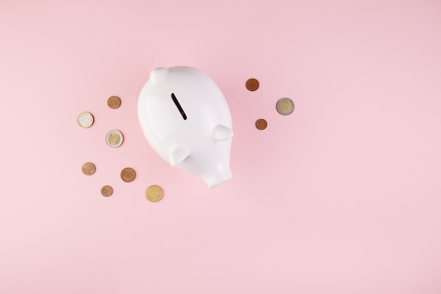 Piggy bank save coin, pink desk background, top view
