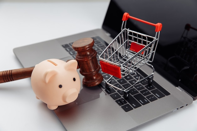 Piggy bank, shopping trolley and wooden hammer on table, online auction concept