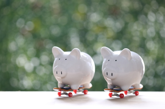 Piggy bank on skateboard with natural green background,business investment and real estate concept